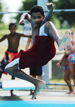 """Globe/T. Rob Brown<br /> D.J. Kress, 12, of Joplin, leaps off the diving board in what he calls, """"Kung Fu Style,"""" at Schifferdecker Park Pool Thursday afternoon, Aug. 2, 2012."""