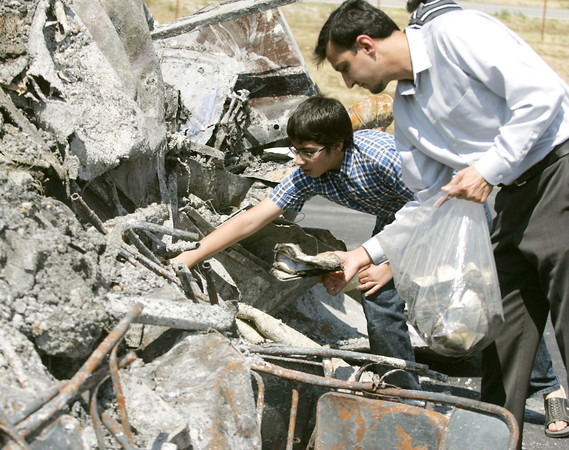 Globe/Roger Nomer<br /> Haaris Rebman, 12, and Hameed Ahmad, of Joplin, look through the remnants of the mosque of the Islamic Society of Joplin for pages of the Quran on Wednesday, Aug. 8, 2012, in Joplin, Mo.