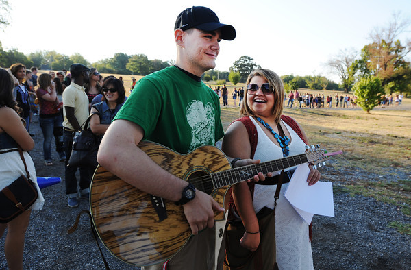 Globe/T. Rob Brown<br /> Logan Rose, of Bentonville, Ark., holds an acoustic-electric guitar owned by hopeful Brittany Moore, of Rogers, Ark., as they wait in a long line at Landreth Park Wednesday morning, Aug. 22, 2012. Moore later made the judges' cut and will move on to the next level of American Idol competition.