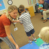 Globe/Roger Nomer<br /> Jennifer Holzwarth organizes her kindergarten students as they line up to have their photo taken with Superintendent CJ Huff on Wednesday at Stapleton Elementary.