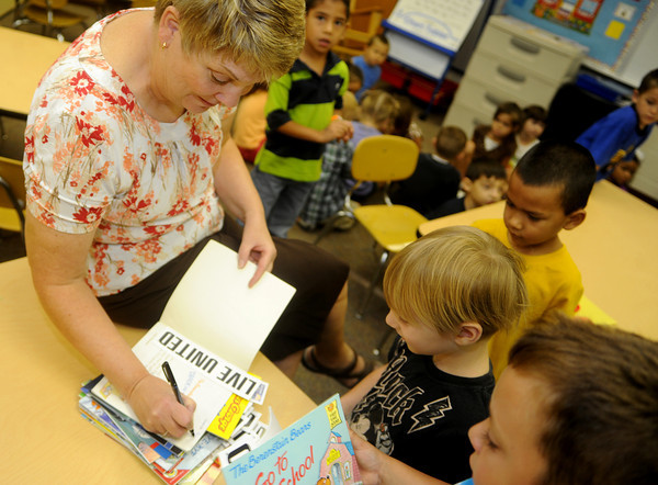 Globe/Roger Nomer<br /> Ann Thompson, kindergarten teacher at Cecil Floyd, writes her students names in their books on Wednesday morning.