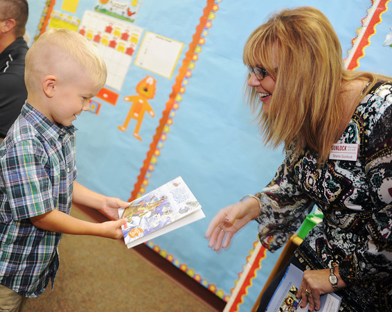 Globe/Roger Nomer<br /> Miles Hogan, a kindergarten student at Cecil Floyd, receives a book from Sheila Gunlock, owner of Gunlock Heating and Air, on Wednesday morning.