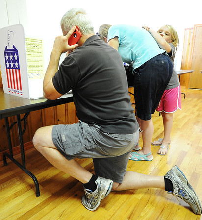 "Globe/T. Rob Brown<br /> Alex Moore, of Silver Creek, ""calls in a lifeline"" as he votes at the Saginaw polling location Tuesday afternoon, Aug. 7, 2012, as 7-year-old Clara Robyn rests on the back of her mother, Katie Robyn, of Saginaw, as she also votes. Moore said he had to call a friend to clarify something on the ballot."