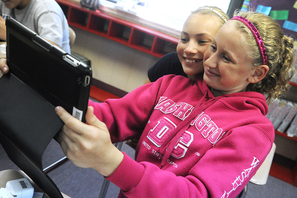 Globe/Roger Nomer<br /> Baxter Springs seventh graders Karissa Howey, left, and Whitney Holstron take a photo with their new iPad on Monday afternoon.