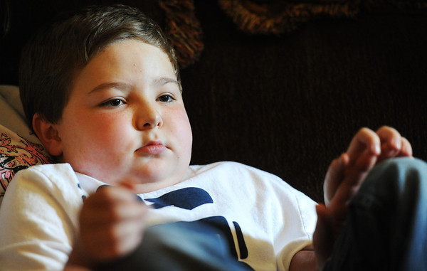Globe/T. Rob Brown<br /> Ten-year-old Dylan Waggoner, of Webb City, holds his mother's hand as he sits on the sofa Tuesday afternoon, Aug. 21, 2012, in his Webb City home. Young Waggoner is in need of a heart transplant.