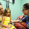 Globe/T. Rob Brown<br /> Five-year-old patient Ava Edwards, of Pittsburg, Kan., is held by her mother Tori Fleck, also of Pittsburg, during her first examination by Dr. Krista Mijares, pediatrician, Friday afternoon, Aug. 3, 2012, at the Community Health Center of Southeast Kansas in Pittsburg.