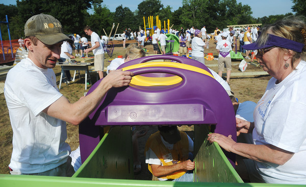 Globe/Roger Nomer<br /> Jonathan Albright, Little Rock, Ark., and Peggy Chapin, Washington, Kan., assemble a piece of playground equipment at North Joplin Headstart on Saturday.