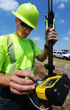 Globe/T. Rob Brown<br /> Larry Nanneman, of Springfield, MoDoT land surveyor, uses a GPS unit at the I-44 and Range Line Road interchange, near the westbound onramp, to verify a land survey done by a contractor Thursday afternoon, Aug. 9, 2012.