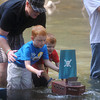 Globe/Roger Nomer<br /> Matt, Carson, 6, and Caden, 4, Osborn release a cardboard boat during the races on Saturday at the Shoal Creek Water Festival.