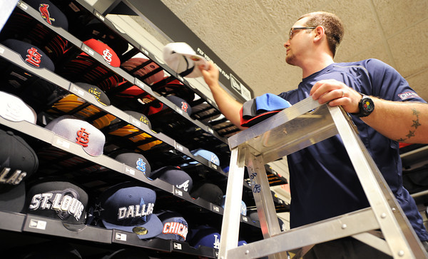 Globe/T. Rob Brown<br /> Jon Fierro, assistant manager at Champ's Sporting Goods in Northpark Mall, restocks the store's hat selection recently.