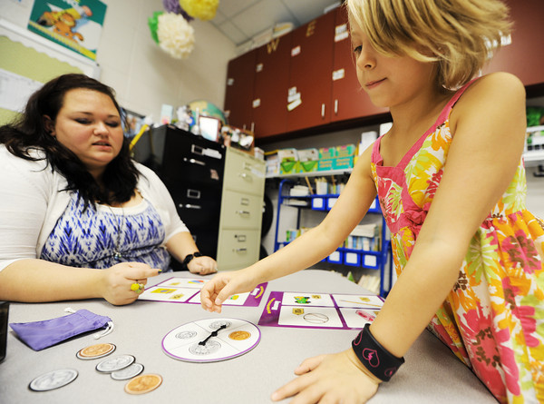 Globe/T. Rob Brown<br /> Kelsey Hendley, a first grader in Ashley Wright's class at McKinley Elementary School, plays a game that teaches monetary values and math in a one-on-one time with Wright during class Wednesday morning, Aug. 29, 2012. The Joplin School District is changing its grading process for students.