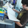 "Globe/Roger Nomer<br /> Daniel Davis, 14, looks through a notebook while attending the ""Tools for School"" event at Frank Fletcher Toyota Scion on Sunday afternoon.  The event gave away school supplies collected by participating businesses."