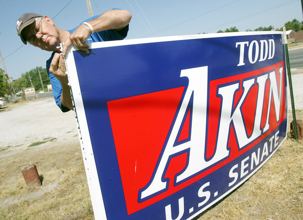 Globe/Roger Nomer<br /> Chairman of Jasper County Republican Central Committee John Putnam rehangs a Todd Akin sign at Seventh and Duquesne on Wednesday morning.