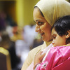 Globe/Roger Nomer<br /> Alina Qidwai holds her daughter Sumayya Khan, 18 months, as she tends to the dessert table during the Eid al-Fitr celebration at the Holiday Inn Convention Center on Sunday.