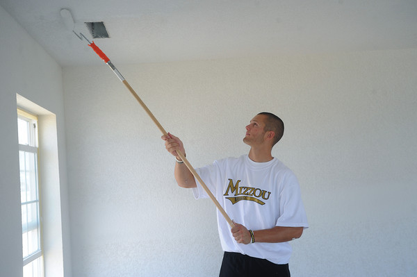 Globe\Roger Nomer<br /> Sean Ullrich, a freshman outfielder with MU baseball team, paints a house along Virginia Street during a visit for Habitat for Humanity on Thursday morning.