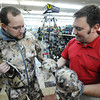 Globe/T. Rob Brown<br /> Customer Brad Ramsey, of Joplin, wears a new marsh waterfowl camouflage vest and jacket by Sitka as salesman Adam Gariglietti shows him a couple matching options for hats Friday afternoon, Aug. 31, 2012, at John's Sport Center in Pittsburg, Kan. This is the first year this particular type of camouflage has been offered.
