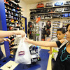 Globe/T. Rob Brown<br /> Lori Wilson, of Coffeyville, Kan., and her son Chuckie Morris, 13, make a school clothes purchase from salesman Jesse Adams at Champ's Sporting Goods in Northpark Mall recently.