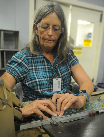 Globe/Roger Nomer<br /> Ann Turner assembles a circuit board to be used in a digital scale at Cardinal Scales on Friday morning.
