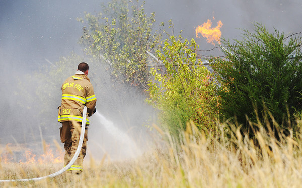 Globe/T. Rob Brown<br /> A Joplin firefighter battles a portion of a controlled burn that moved into a grassy field just south of the old Route 66 Speedway Thursday afternoon, Aug. 30, 2012.