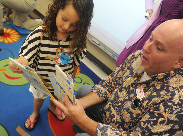 Globe/Roger Nomer<br /> Jionna Leonetti-Houchin, a kindergarten student at Stapleton Elementary, selects a book from Bryan Shank, general manager of Gunlock Heating and Air, on Wednesday morning.