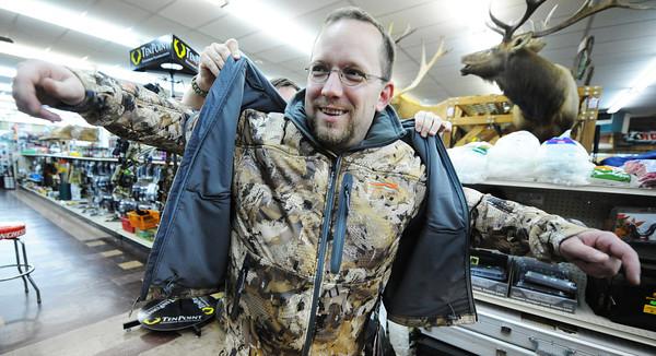 Globe/T. Rob Brown<br /> Customer Brad Ramsey, of Joplin, gets assistance from salesman Adam Gariglietti in trying on a new marsh waterfowl camouflage vest and jacket by Sitka Friday afternoon, Aug. 31, 2012, at John's Sport Center in Pittsburg, Kan. This is the first year this particular type of camouflage has been offered.