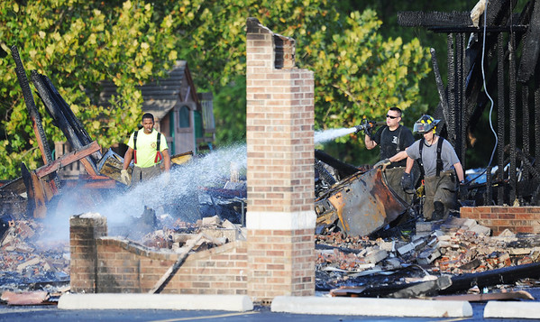 Globe/T. Rob Brown<br /> Carl Junction firefighters extinguish the smoldering remains of the Islamic Society of Joplin mosque Monday morning, Aug. 6, 2012.