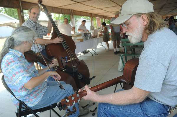 Globe/Roger Nomer<br /> (from top) Bruce Harvey and LeeAnn and Jack Sours perform as the Hairy Vetch String Band at the Webb City Farmers Market on Friday afternoon.