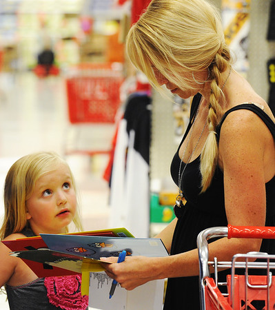 Globe/T. Rob Brown<br /> Brooke Vonder Haar looks up for the response of her mother, Sarah Vonder Haar, of Webb City, to see which Angry Birds folders she can get while shopping for school supplies Monday afternoon, Aug. 6, 2012, at Target in Joplin.