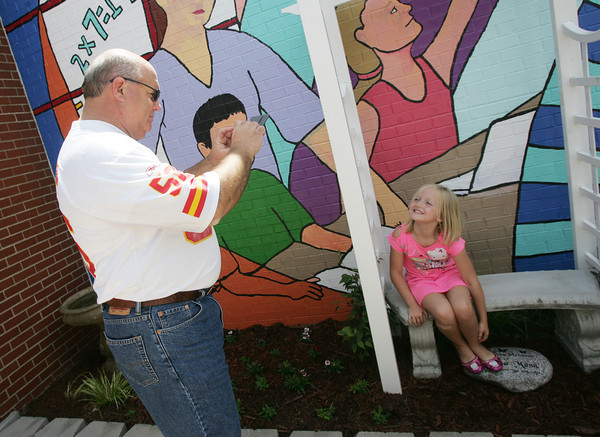 Globe/Roger Nomer<br /> Rick Stockton, Empire District construction designer, takes a photo of Hannah Bradley, 3rd grader at Jefferson Elementary, at the school's new outdoor space on Thursday.  Empire was one of the sponsors of the outdoor space.