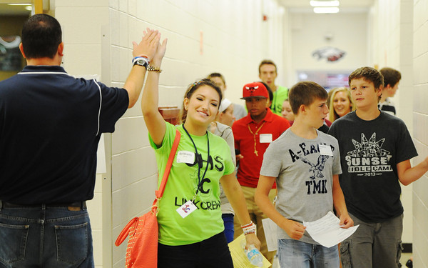 Globe/T. Rob Brown<br /> Joplin High School junior Brittany Morris (center) gets a high-five from Assistant Principal Matt Harding as she leads a group of incoming freshman on a tour Thursday afternoon, Aug. 8, 2013, at the freshman and sophomore campus.