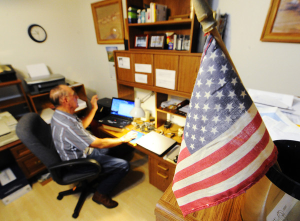 Globe/T. Rob Brown<br /> Under the red, white and blue of a flag that belonged to his father, Charlie Bridges of Diamond reviews a Powerpoint presentation he created about his father Walter Bridges, who was a World War I veteran, Monday morning, Aug. 5, 2013.