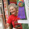 Globe/Roger Nomer<br /> Elma Hurt, Pittsburg, helps hang up the overall champion quilt, made by Noralee Chadd, at the Little Balkans Days quilt show in the basement of Memorial Hall on Friday.