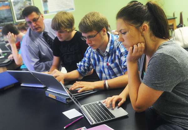Globe/Roger Nomer<br /> (from left) Forensic Science teacher George Thornton, Webb City High sophomores Matthew Burkhart, Christian Kilby and Hannah Kuhns use their Chromebooks on the first day of class on Wednesday.  This is the first year the school has made the Chromebooks available to every student, in order to boost interaction and open resources.
