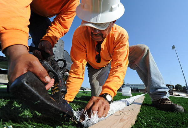 Globe/T. Rob Brown<br /> Samuel Samudio, right, places white artificial turf down for the new football field at NEO with help from fellow FIeld Turf Crew installer Rudy Alvarado operating an adhesive gun Thursday evening, Aug. 1, 2013, in Miami, Okla.