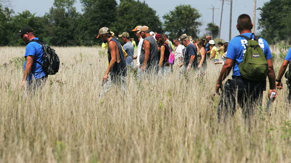Globe/Roger Nomer<br /> Searchers comb a field near 100 Lane west of Golden City on Wednesday afternoon.