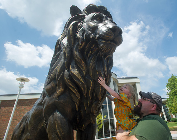 Globe/Roger Nomer<br /> Lyra Morris-Burrow, 3, hugs the new lion statue with help from her dad Lyndall Burrow, assistant tech director at the MIssouri Southern theatre department, after Monday's unveiling.