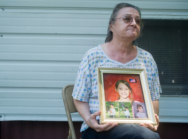 Globe/Roger Nomer<br /> Velma Horton, grandmother of Adrianna Horton, holds photos of the missing girl as she talks about search efforts during an interview at her home in Golden City on Tuesday afternoon.