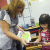 "Globe/Roger Nomer<br /> Sheila Gunlock gives a book she authored called ""Groovy Granny and the Character Bees"" to kindergartner Kadyn Daniel at Cecil Floyd Elementary on Thursday."