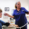 Jane Fillmore, registered medical assistant, (left) takes the temperature and blood pressure of patient Michael Weaver of Duquesne Thursday morning, Aug. 29, 2013, at the Community Clinic in Joplin. The clinic is one of the many organizations that receives funding from the United Way.<br /> Globe | T. Rob Brown