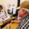 Patient Larry Wood of Joplin looks on as Doris Carson, R.N., works through his discharge paperwork Thursday morning, Aug. 29, 2013, at the Community Clinic in Joplin. The clinic is one of the many organizations that receives funding from the United Way.<br /> Globe | T. Rob Brown