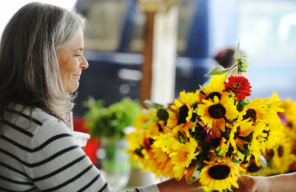 Globe/T. Rob Brown<br /> Beth Willis of Webb City smiles as she decides on her favorite boquet of sunflowers and zinnias Friday afternoon, Aug. 9, 2013, at the Webb City Farmers Market. She purchased the flowers from Mai K. Lor of Rocky Comfort.