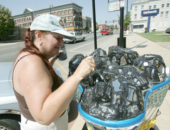 "Globe/Roger Nomer<br /> Merri Teresa Accad, Pittsburg, does some touch-up painting on her coal bucket called ""Reflections"" in downtown Pittsburg on Friday."