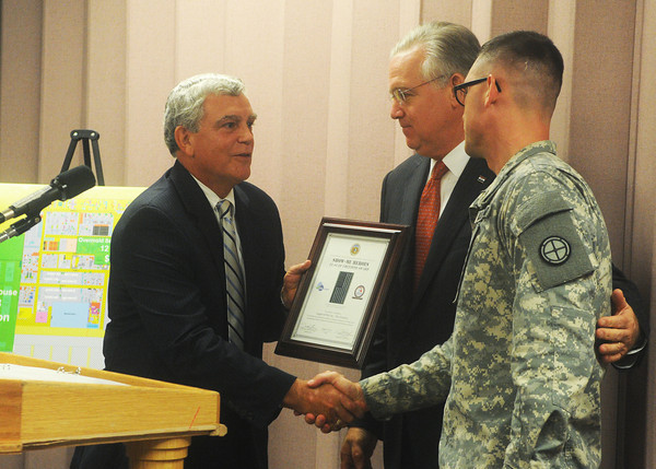 Globe/Roger Nomer<br /> Gov. Jay Nixon with Missouri National Guard Lt. Jon Barry, director of the Show Me Heroes program, right, present David Haffner, Leggett and Platt Chief Executive Officer and Chairman of the Board of Directors, with the Flag of Freedom Award on Wednesday.  The award recognizes businesses that make an effort to hire veterans.