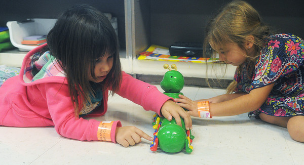 Globe/Roger Nomer<br /> Kindergartners Roxie Allen, left, and Emily McGuirk get acquainted with toys and each other during the first day of class at Soaring Heights Elementary on Thursday.  The students will move into a new building this school year.
