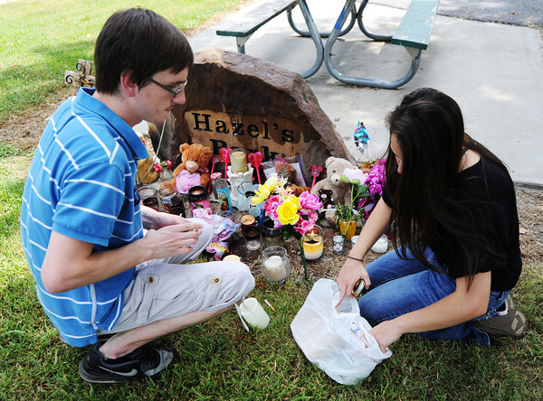 Kenton and Meagan Jackson of Grove, Okla., cousins of Adriaunna Horton, add candles to a memorial Wednesday afternoon, Aug. 28, 2013, at Hazel's Park.<br /> Globe | T. Rob Brown