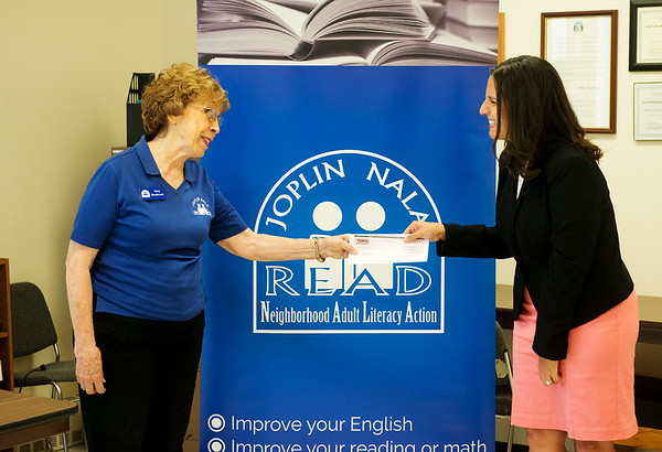Globe/Roger Nomer<br /> Stephanie Onstot, community relations associate for TAMKO Building Products, presents Marj Boudreaux, executive director of Joplin Neighborhood Adult Literacy Action, with a check for $5,000 from TAMKO on Thursday. Boudreaux said that after funding cuts to NALA, the check would help with continueing their mission for adult literacy.