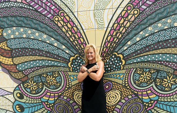 Globe/Roger Nomer<br /> Lori Ann Spachek, a State Farm agent in Pittsburg, poses for a photo and demonstrates the interactive element of the butterfly mural on Wednesday in Mercy Park. State Farm and Walmart are sponsors of the mural.