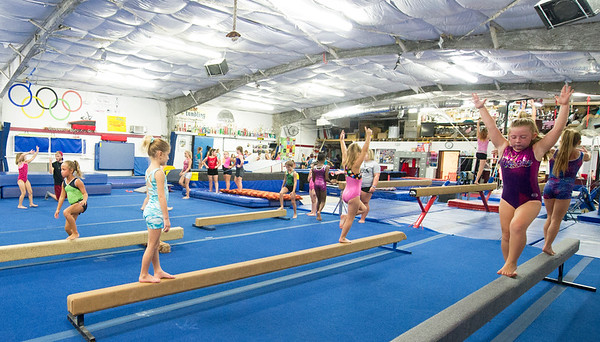 Young girls work out on the balance beam during classes on Wednesday night at The Flip Shop.<br /> Globe | Laurie Sisk