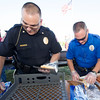 From the left: Major Sloan Rowland and Officer Mike Gayman, both of the Joplin Police Department,  pass out some of the 800 hotdogs provided by the JPD during the National Night Out 2016 on Tuesday night at Cunningham Park. Food 4 Less provided chips, Price Cutter provided buns and Target provided school supplies for the event.<br /> Globe | Laurie Sisk