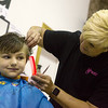 Globe/Roger Nomer<br /> Kristy Mjelde, with the Hair Shop in Frontenac, gives Maria Pierce, 8, a haircut on Monday during Victory Life Church's back to school event. Organizers estimated they would give 500 haircuts during the event.